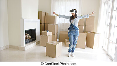 Happy young woman enjoying her VR headset prancing around in...