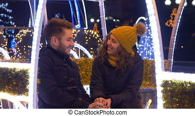 Lovers holding hands and laughing at each other in Christmas fair