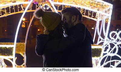 Lovers kissing and hugging in the downtown Christmas market in nighttime