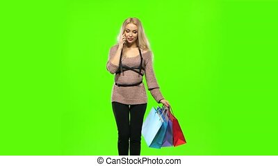 Blonde girl carries a multi colored packages, talking on the...