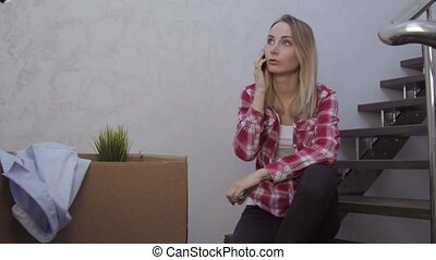 Attractive young woman sitting on a staircase using her mobile phone