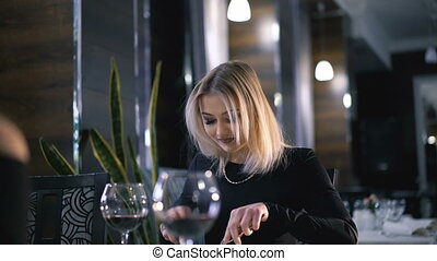 Stylish blonde eating at fashionable restaurant in 4K