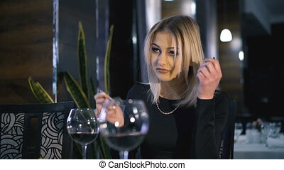 Stylish girls eating, drinking wine and speaking at...