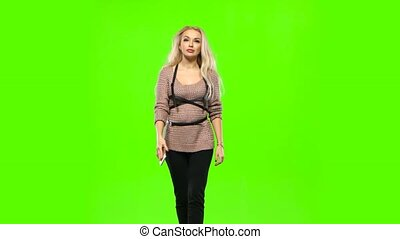 Girl with long curly hair talking on the phone. Green screen