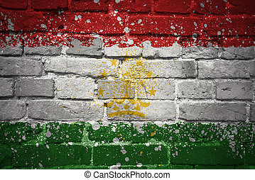 painted national flag of tajikistan on a brick wall -...