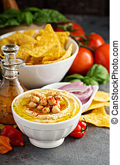 Homemade hummus in a white bowl with vegetables and corn...