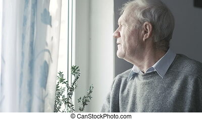 Portrait of old handsome man looking at windows and smiling to camera