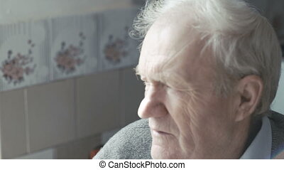 Portrait of old man sitting near the window and looking at...