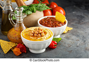 Homemade hummus and tomato salsa in white bowls with...