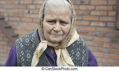 Portrait of very old woman with sadness in eyes smiling to camera in 4K