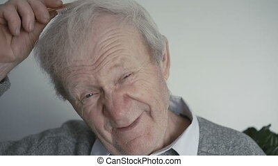 Wrinkled senior is combing his gray hair with a wooden comb