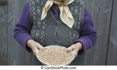 Portrait of very old smiling woman with bowl of wheats'...