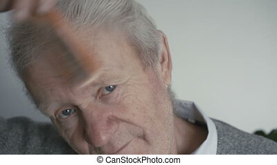 Wrinkled happy senior is combing his gray hair with comb
