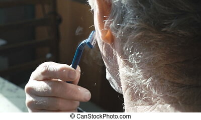 Senior shaving beard at home by himself in village