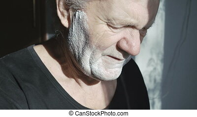 Old man shaving beard at home by himself in 4K.