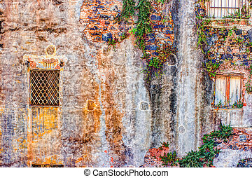 red vintage old brick wall with windows and green ivy -...