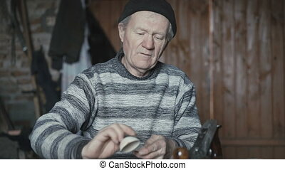 Old wrinkled man hewing his handmade wooden spoon and...