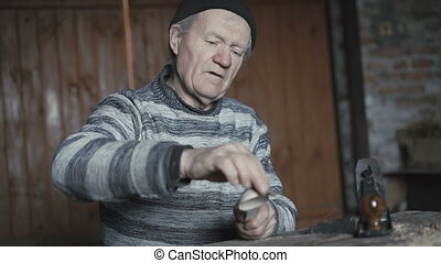 Happy wrinkled man hewing his handmade wooden spoon and...