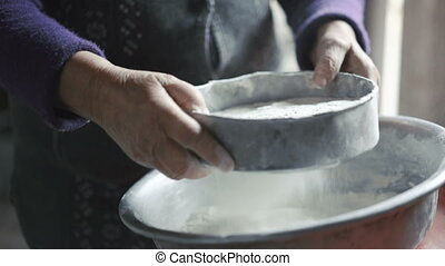 Wrinkled old woman sifting flour
