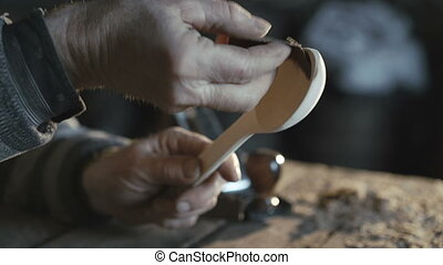 Close up of old carpenter's hands making wooden spoon