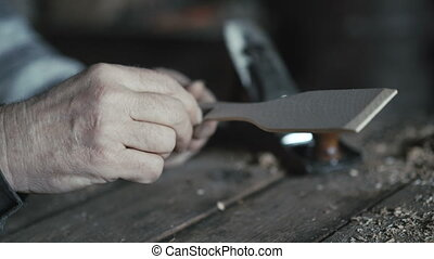 Old wrinkled man hewing his handmade wooden spoon 4K.