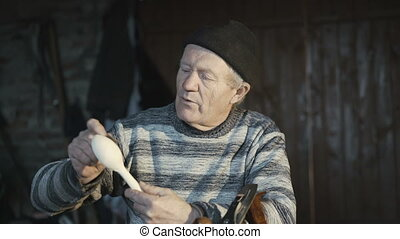 Old wrinkled man showing his handmade wooden spoon and...
