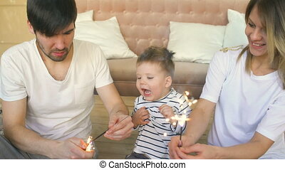 Young father and mother celebrate their son birthday burning sparklers at home and smiling