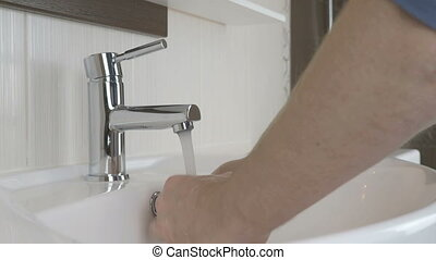 Man washing hands in the bathroom