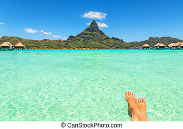 Female crossed legs over tropical blue lagoon and Otemanu...