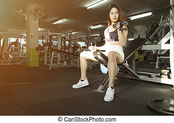 Fitness woman showing exercises in sport gym