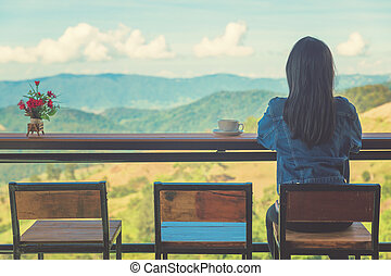 Woman sit in cafe, drink hot coffee in resort in Thailand....