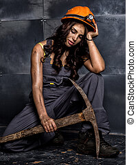 sexy female miner worker with pickaxe, in coveralls sitting...