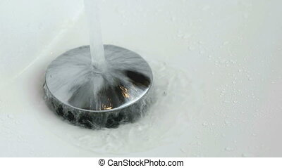 The process of draining water into the white sink. Close-up