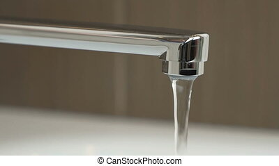 Water under weak pressure flows from a water tap - Water...