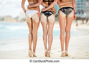 Three sexy women's butt in the sand on the beach. - Three...