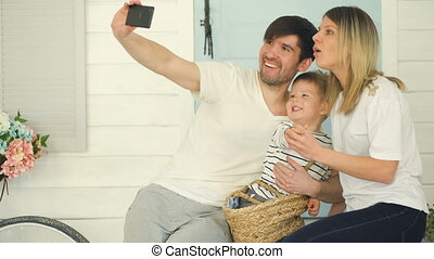 Father of happy family make selfie with his wife and little son in front their home door