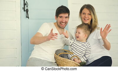 Happy smiling family waving hands and posing into camera at home