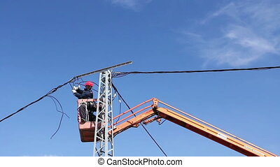 High elevated cherry picker with team of electrician's who are working on power line, pole