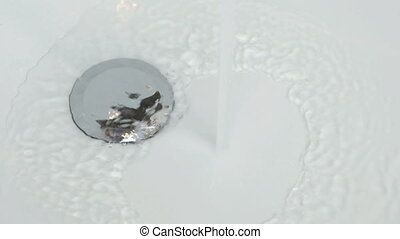 Filling of water into white bathtub. Close-up