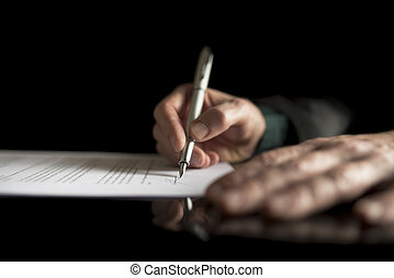 MAle hand signing contract - Low angle view of a male hand...
