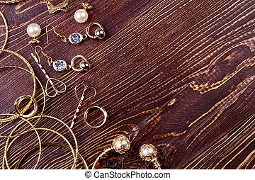 Jewelry on wooden surface. Bracelets, rings and earrings....