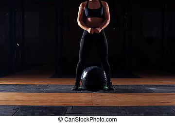 Muscular girl working out with heavy ball - Muscular girl in...