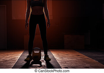 Young sporty girl preparing for kettlebell workout. Muscular...
