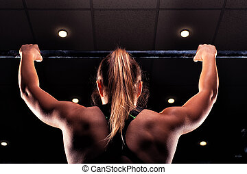 Strong blonde girl doing pull up exercise in gym