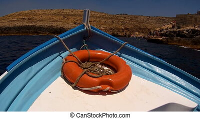 Front view boat with lifebuoy,floating on blue sea.