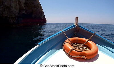 Front view boat with lifebuoy,floating on blue sea. - Front...