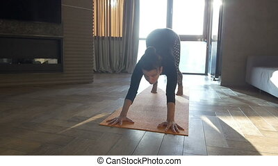 Fit woman doing yoga on mat at home in the bedroom....