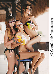 Three beautiful girls in a bar on the beach, on the ocean. -...