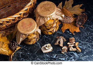 Two glass jars with wild pickled mushrooms and dry white wild mushrooms on black marble background.