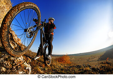 low angle view of cyclist standing with mountain bike...